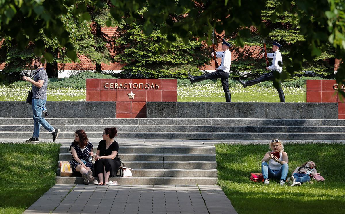La gente difruta de un día soleado mientras hay un cambio de guardia en los jardines Aleksándrovski.