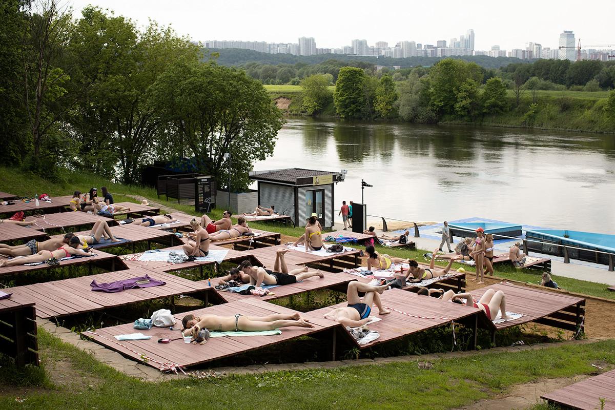 Orang-orang berjemur di salah satu taman di tepi Sungai Moskow selama hari yang panas di ibu kota, Rusia, Selasa, 9 Juni 2020.