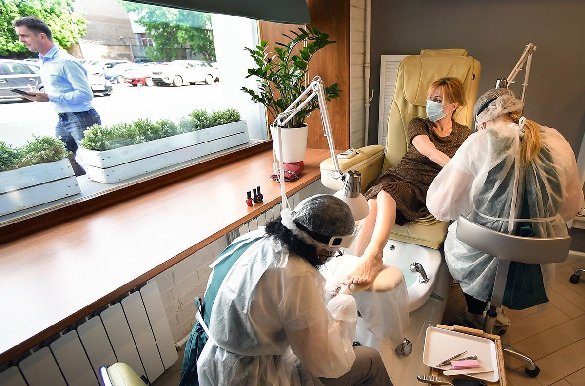 Majstorice manikure i pedikure rade na klijentici u salonu