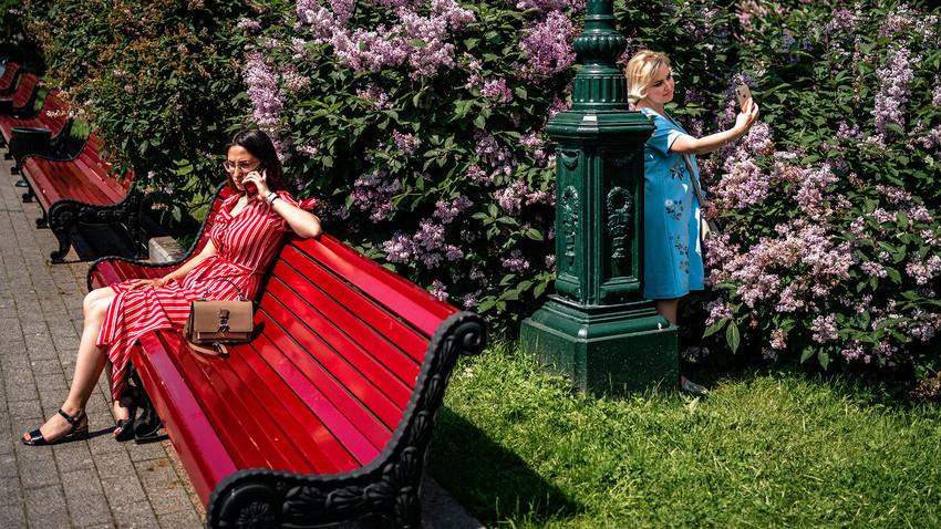 Ženske uživajo v toplem in sončnem dnevu v parku v centru Moskve, 9. junija 2020, prvi dan po tem, ko je Moskva odpravila vrsto omejitvenih ukrepov, vključno s strogo samoizolacijo, ki so jih vzpostavili za zaustavitev širjenja bolezni COVID-19, ki jo je povzročil novi koronavirus.