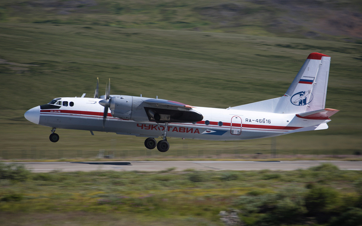An-24 RV air liner belonging to Chukotavia airlines seen above the take-off runway of an airport