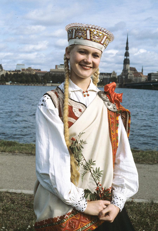 Una joven con un traje tradicional letón en los muelles de Riga