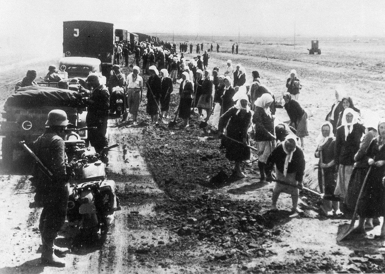Cоветские граждане на дорожных работах под надзором немецких солдат.
