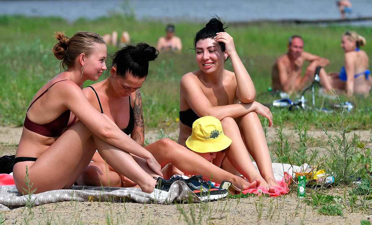 Девушки загорают на берегу Абаканской протоки Енисея в Красноярске.