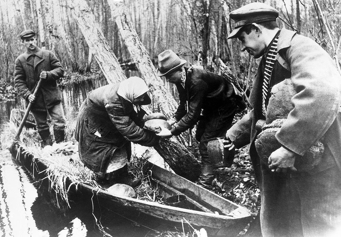 Domačini prinašajo zalege hrane partizanom v beloruskih gozdovih.