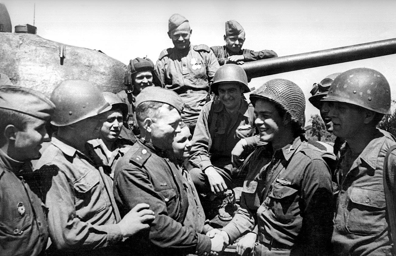 Komandan tank Letnan Georgy Lovchikov (ketiga dari kiri) berjabat tangan dengan Letnan Tentara AS Jack Haltgraves.