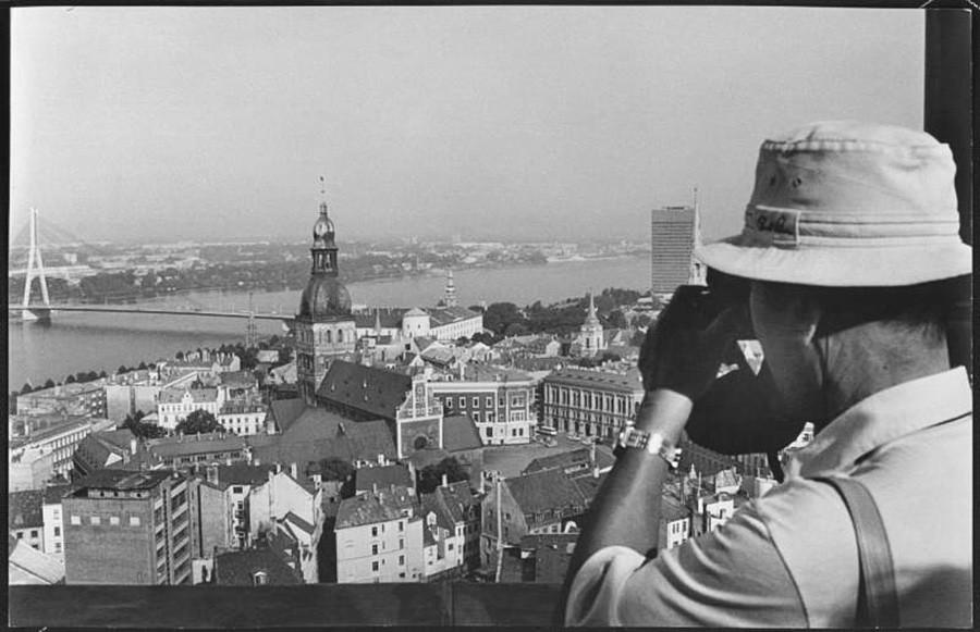 1978 година. Фотографот Виктор Рујкович ја снима панорамата на градот. Кулата на Домската катедрала, зад неа Мостот преку реката Даугава.