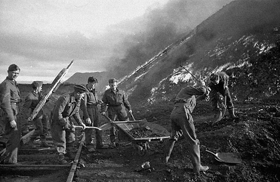 Los zapadores de la 3ª Compañía de Campo, Ingenieros Reales Canadienses, quemando pilas de carbón.