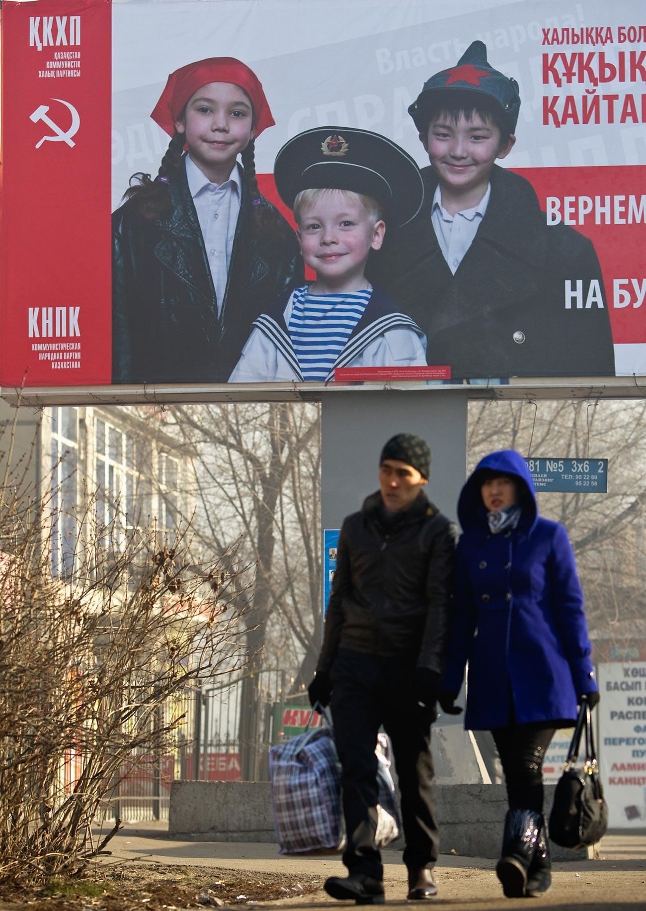 Orang-orang melewati poster pemilu Partai Rakyat Komunis Kazakhstan (QKHP) di Almaty.
