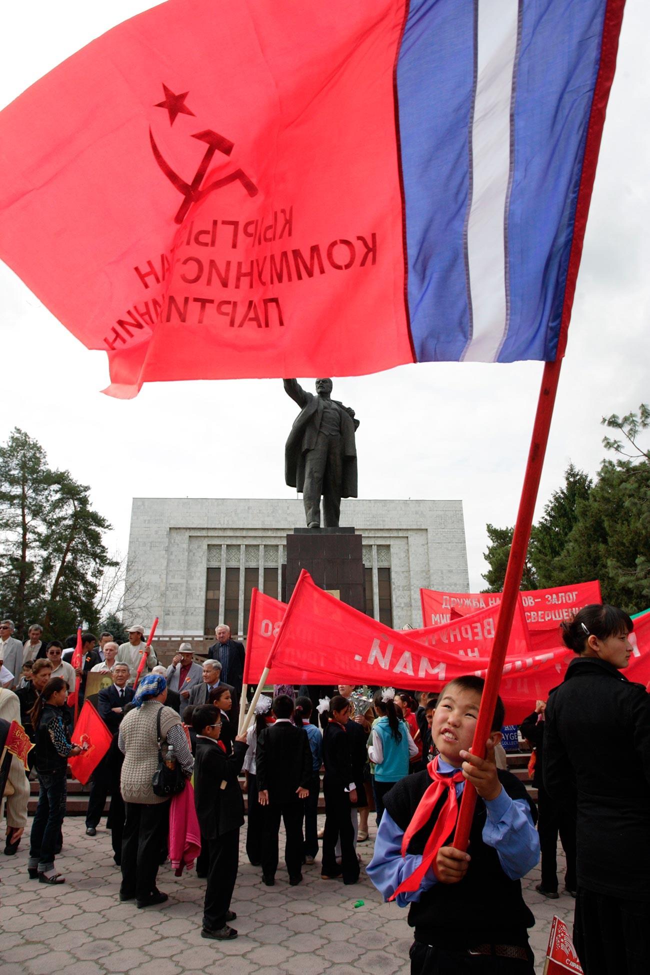 Seorang anak laki-laki mengibarkan bendera komunis selama perayaan Hari Buruh Internasional di Bishkek.
