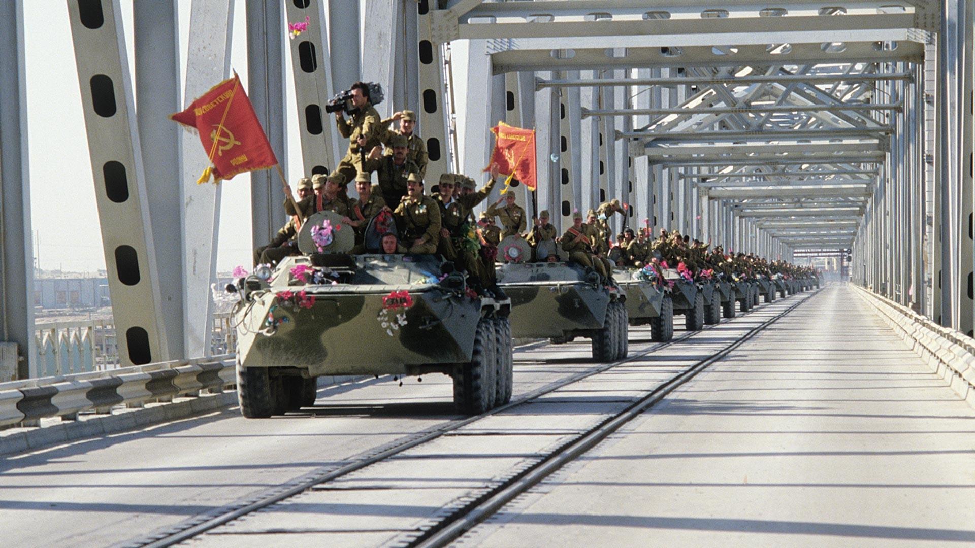 A column of armored vehicles crosses the Afghan-Soviet border through the Friendship bridge lying over the Amu Darya river.