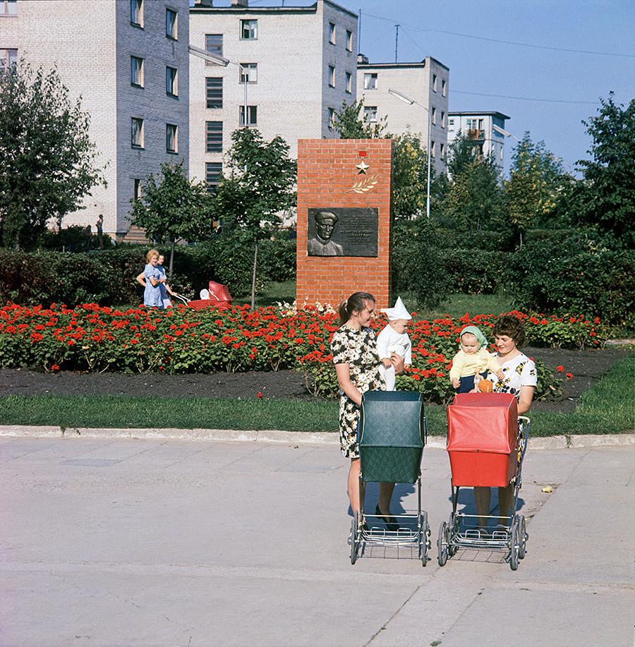 De jeunes mères dans la ville de Novoloukoml avec, en fond, le monument au commandant de détachement de partisans Fiodor Ozmitel, 1978