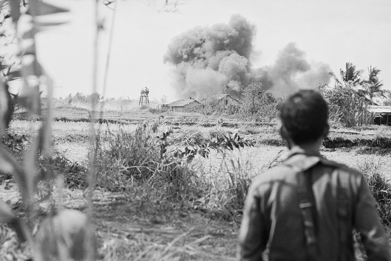 Vietnamese soldier watching explosion during the Vietnam War.