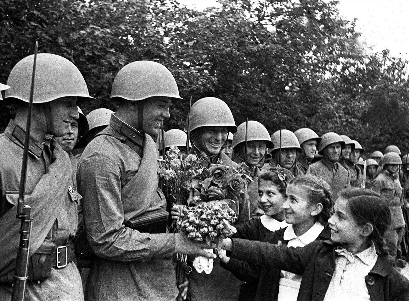 Soldados do Exército Vermelho são recebidos por crianças durante um desfile militar celebrando a incorporação da Bessarábia e da Bucovina do Norte à URSS, Quichinau, em 4 de julho de 1940