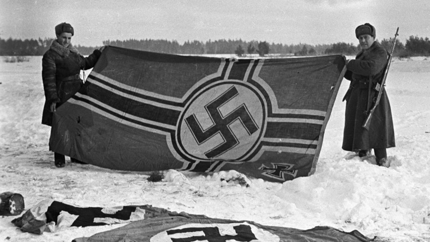 Dois soldados soviéticos mostrando primeira bandeira nazista capturada em batalhas perto de Kalinin, 1941