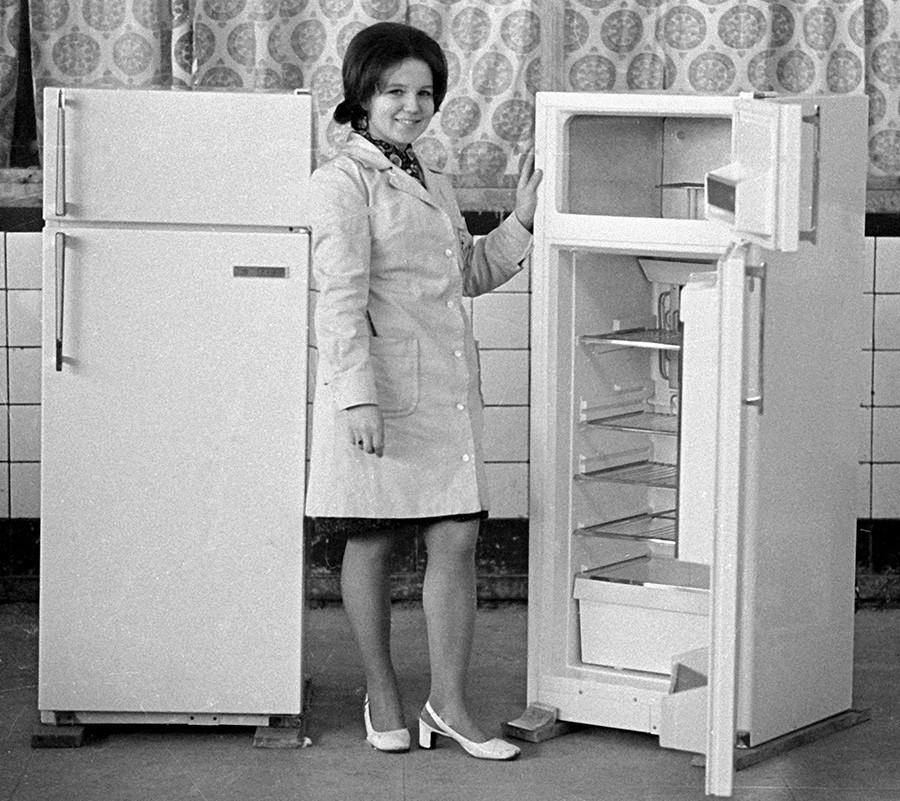 Funcionário da Fábrica de Refrigeradores de Minsk demonstrando a geladeira Minsk-7, 1973. Metade de todas as casas soviéticas tinha uma dessas