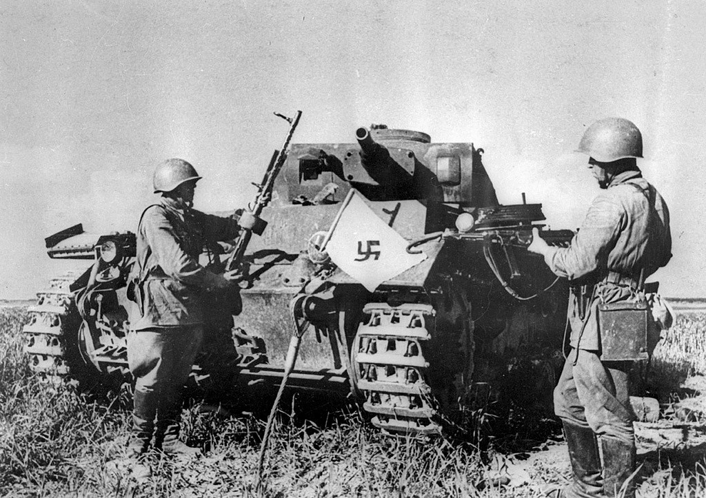 Tentara Soviet di sebelah tank Jerman yang rusak, Mogilev, 1941.