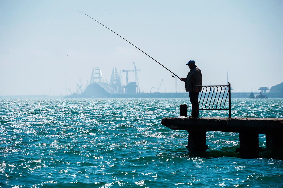 Moški lovi ribe na mestnem nabrežju v Kerču.