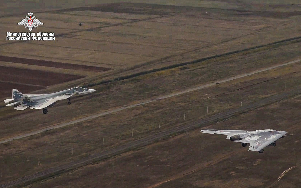 """Првиот заеднички лет на тешкиот борбен дрон Сухој С-70 """"Охотник"""" и ловечкиот авион Су-57. Во рамките на тестирањата """"Охотник"""" успешно изведе лет без пилот во зона на воздушна опасност. Русија, 27 септември 2019 година"""
