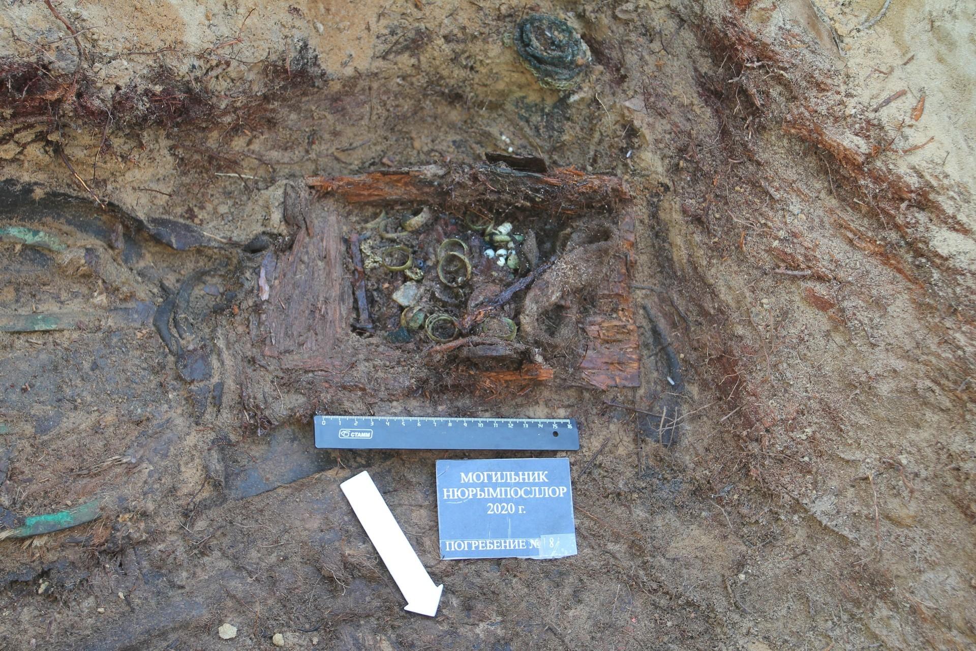 Caja de madera con joyas. (14 anillos y collares de cobre) en la tumba de una mujer