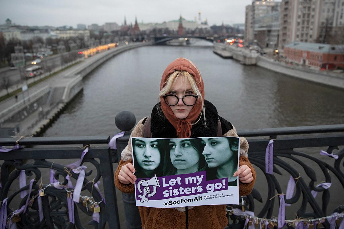 Eine Frau hält ein Schild mit Fotos von Chatschaturjan-Schwestern während einer Aktion gegen häusliche Gewalt in Moskau