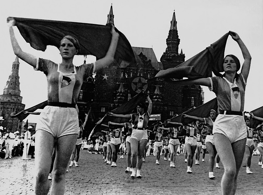 Para perempuan membawa syal. Parade olahraga di Lapangan Merah.