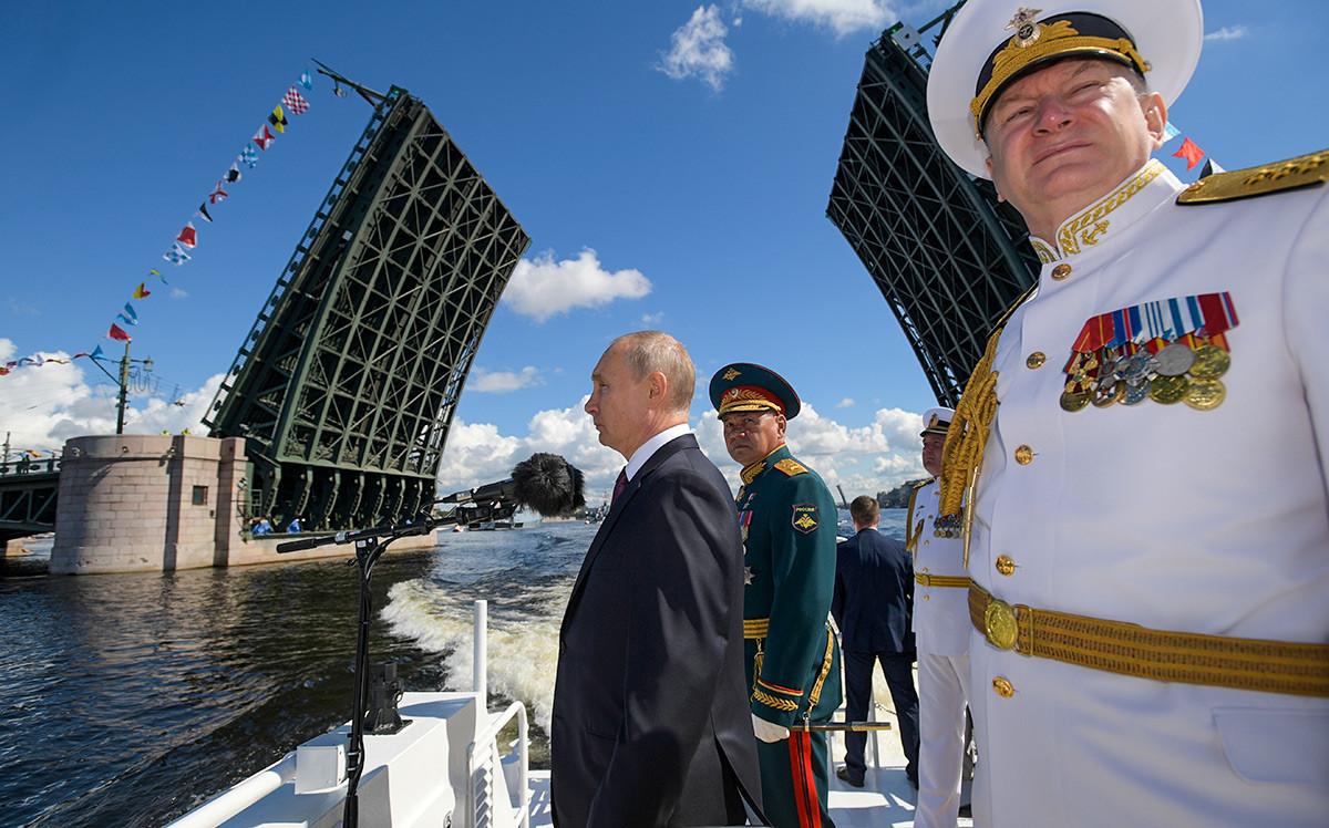 Le président russe Vladimir Poutine, le ministre de la défense Sergueï Choïgou et le commandant en chef de la marine russe, Nikolaï Evmenov, inspectent des navires de guerre sur la Neva lors du défilé de la Journée de la Marine.