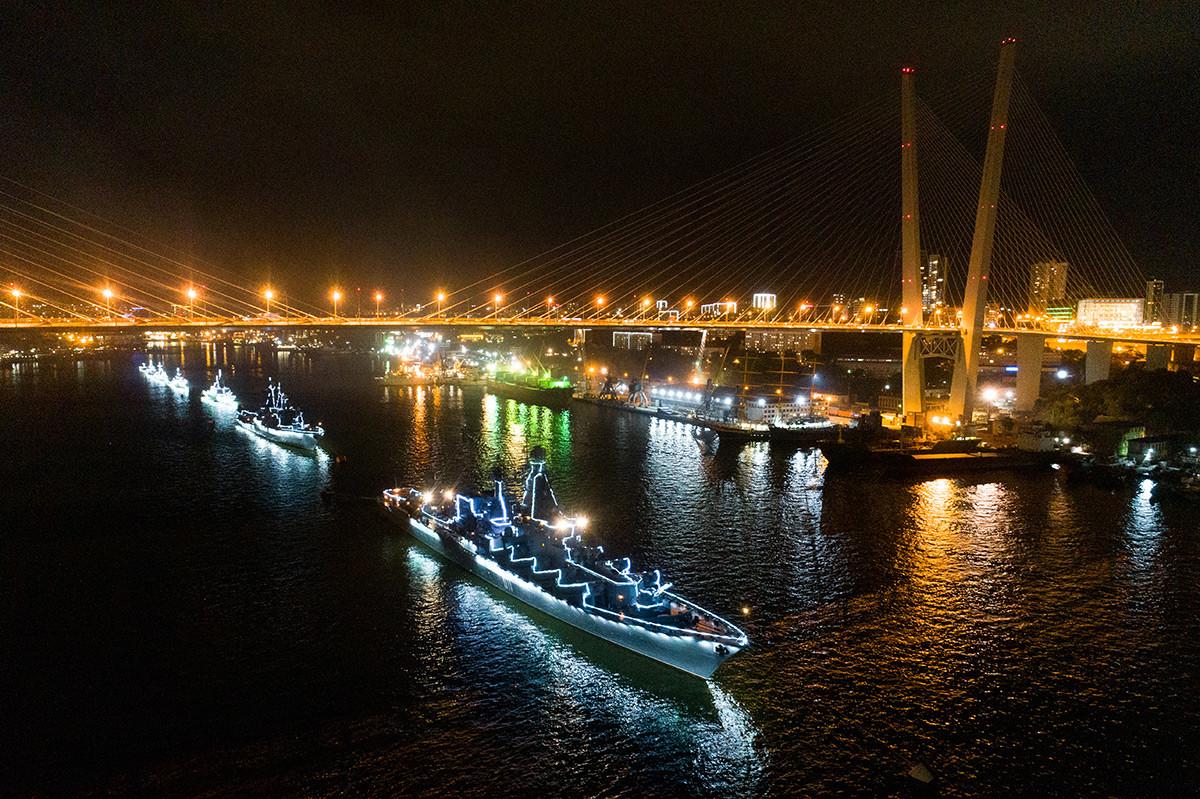 Des navires illuminés de la Flotte du Pacifique paradent dans la baie de la Corne d'Or, à Vladivostok.
