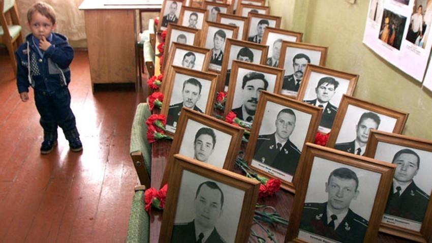 Un niño junto a los retratos de las víctimas del submarino Kursk, en sus barracas, durante la ceremonia conmemorativa en el puerto Ártico de Vidiádevo.