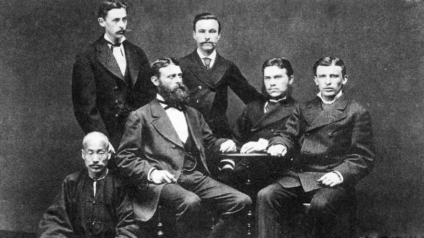 """Управлението на компанията """"Кунст и Алберс"""" на последната среща във Владивосток през 1880 г. На масата са (отляво надясно): Густав Алберс, Густав Кунст и Адолф Датан, зад тях стоят датчанинът Антон Нилсен (вляво) и М. М. Дмитриев (вдясно), По-долу е Чи Мо Чен, който е шеф на китайските работници"""
