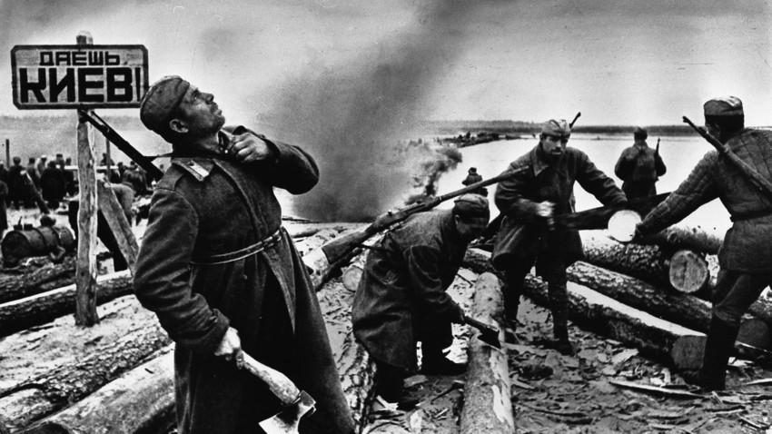 """Soldati sovietici preparano le zattere per attraversare il fiume Dnepr (il cartello dice """"A Kiev!""""). Battaglia del Dnepr, 1943"""