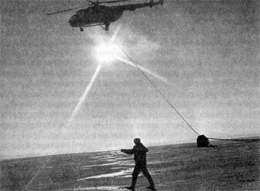 Mengangkut kapsul antariksa berparasut dengan helikopter.