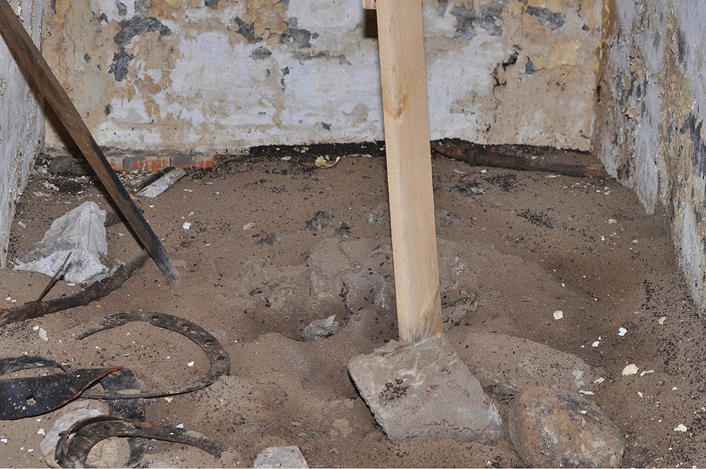 Kupček zemlje, ki so ga mravlje skoraj povsem zapustile, na dnu bunkerja pozimi, štiri mesece po postavitvi »stezice«. Vidi se »mravlja pokopališča« okoli kupčka in ob zidovih.
