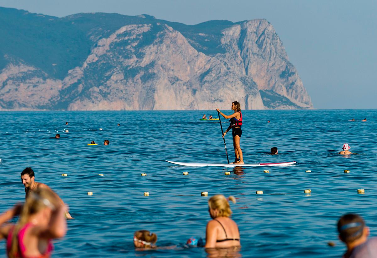 Девојка весла стојећи на дасци за сурфовање (SUP). Акваторија Јасписне плаже код рта Фиолент, Севастопољ.