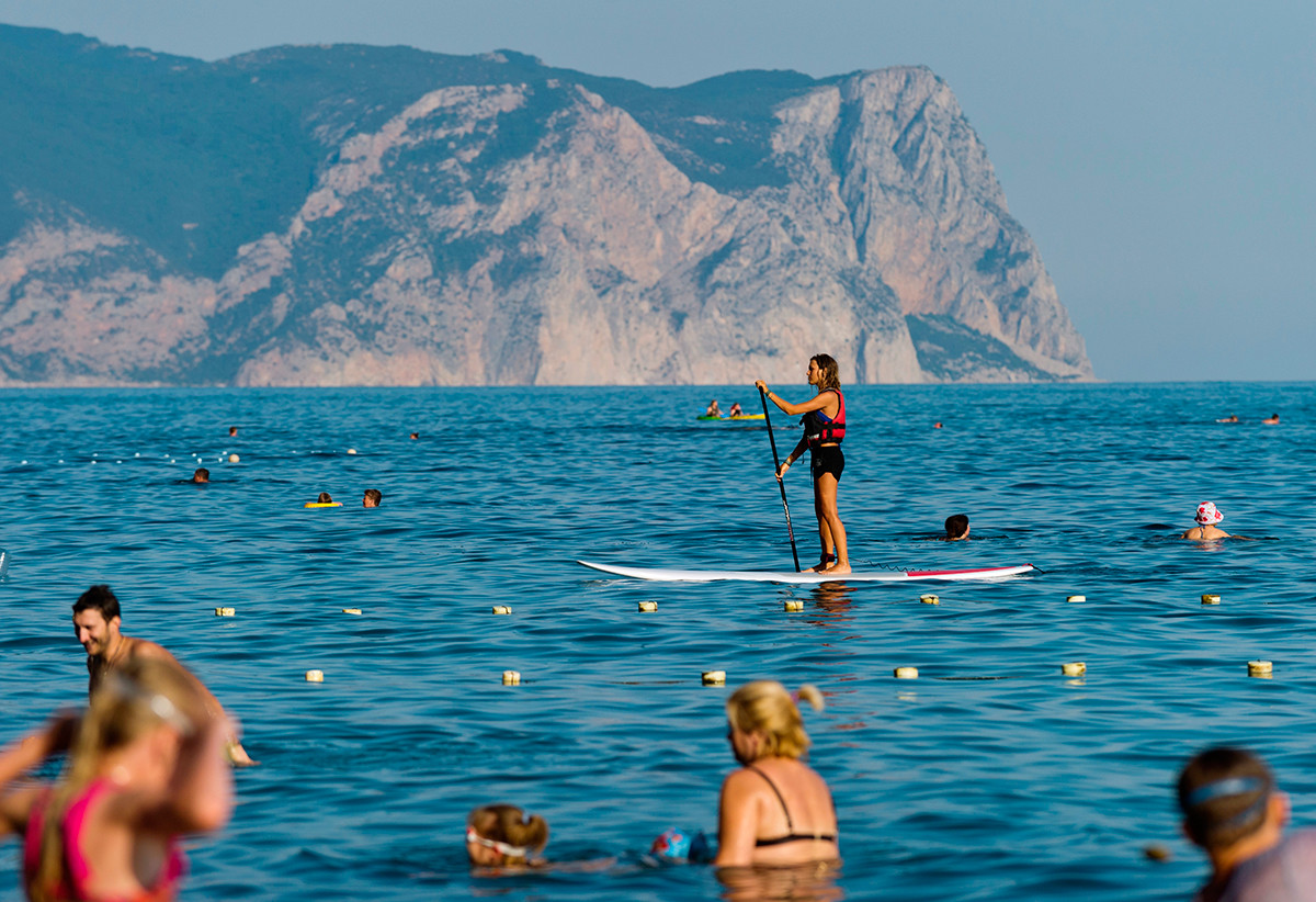 The girl is engaged in SUP surfing in the waters of the Jasper beach at Cape Fiolent in Sevastopol