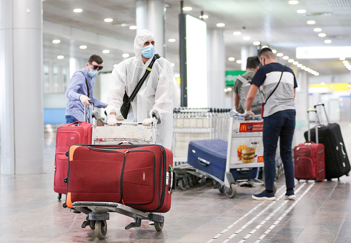People who have arrived from New York City on an Aeroflot - Russian Airlines flight, carry their luggage at the arrivals area of Sheremetyevo International Airport. June 17.2020