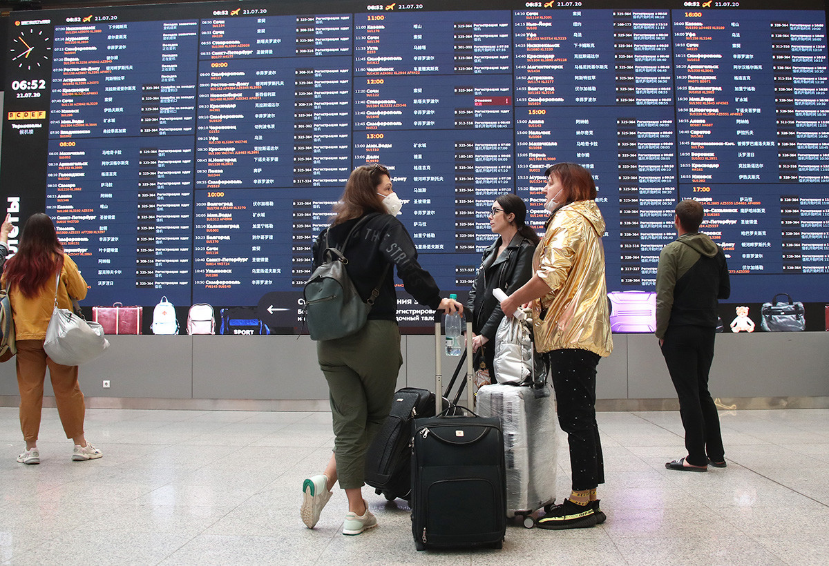 People near an information board at Terminal B at the Sheremetyevo International Airport near Moscow during the pandemic of the novel coronavirus disease (COVID-19), july 21,2020