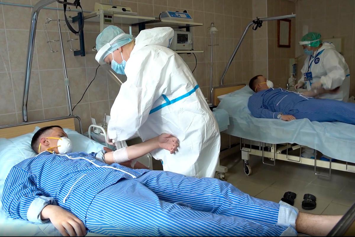 """Кадар од видеоснимка што МО на Русија го стави на располагање во среда 15 јули 2020 година. Медицински работници во заштитна опрема се подготвуваат да вадат крв на доброволци кои учествуваат во тестирањето на вакцината од коронавирусот во Главната воена болница """"Бурденко"""" во близина на Москва."""