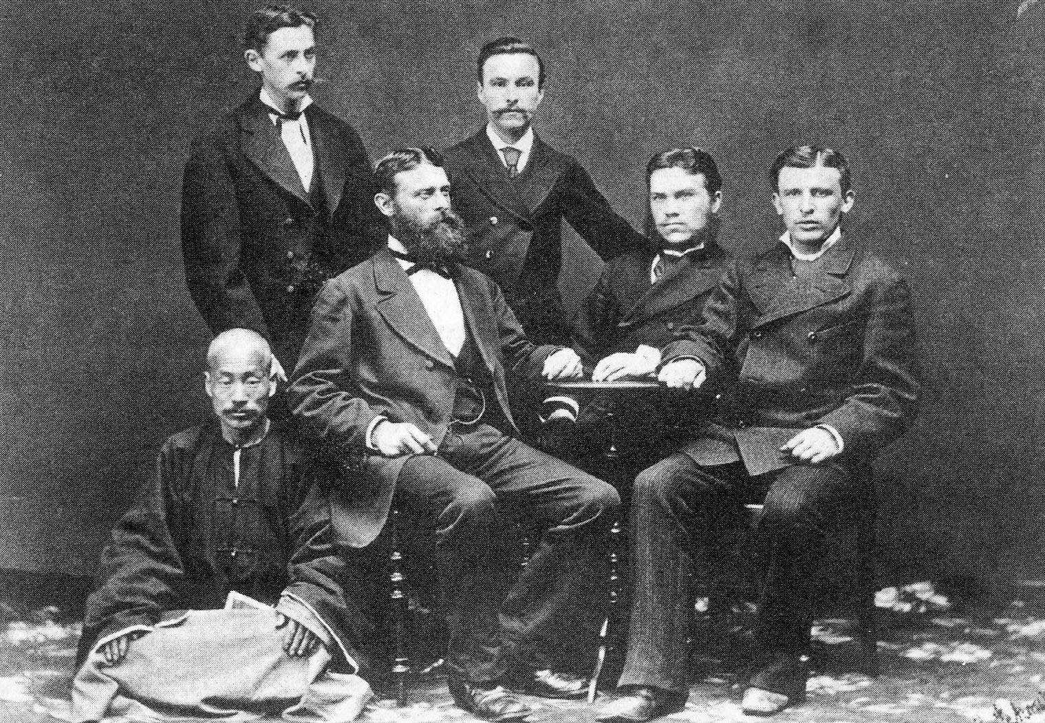 """Руководство фирме """"Кунст и Алберс"""" на последњем сусрету у Владивостоку 1880. За столом су (слева надесно): Густав Алберс, Густав Кунст и Адолф Датан, иза њих су сарадници Данац Антон Нилсен (лево) и М.М.Дмитријев (десно). Доле је Чи Мо Чен, који је био шеф кинеским радницима."""