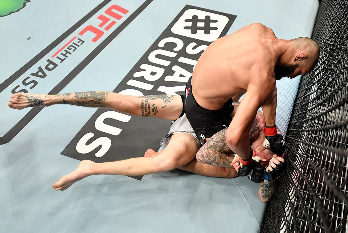 Jamzat Chimaev (con guantes rojos) golpea a Rhys McKee (guantes azules) de Irlanda del Norte en su pelea de peso welter.
