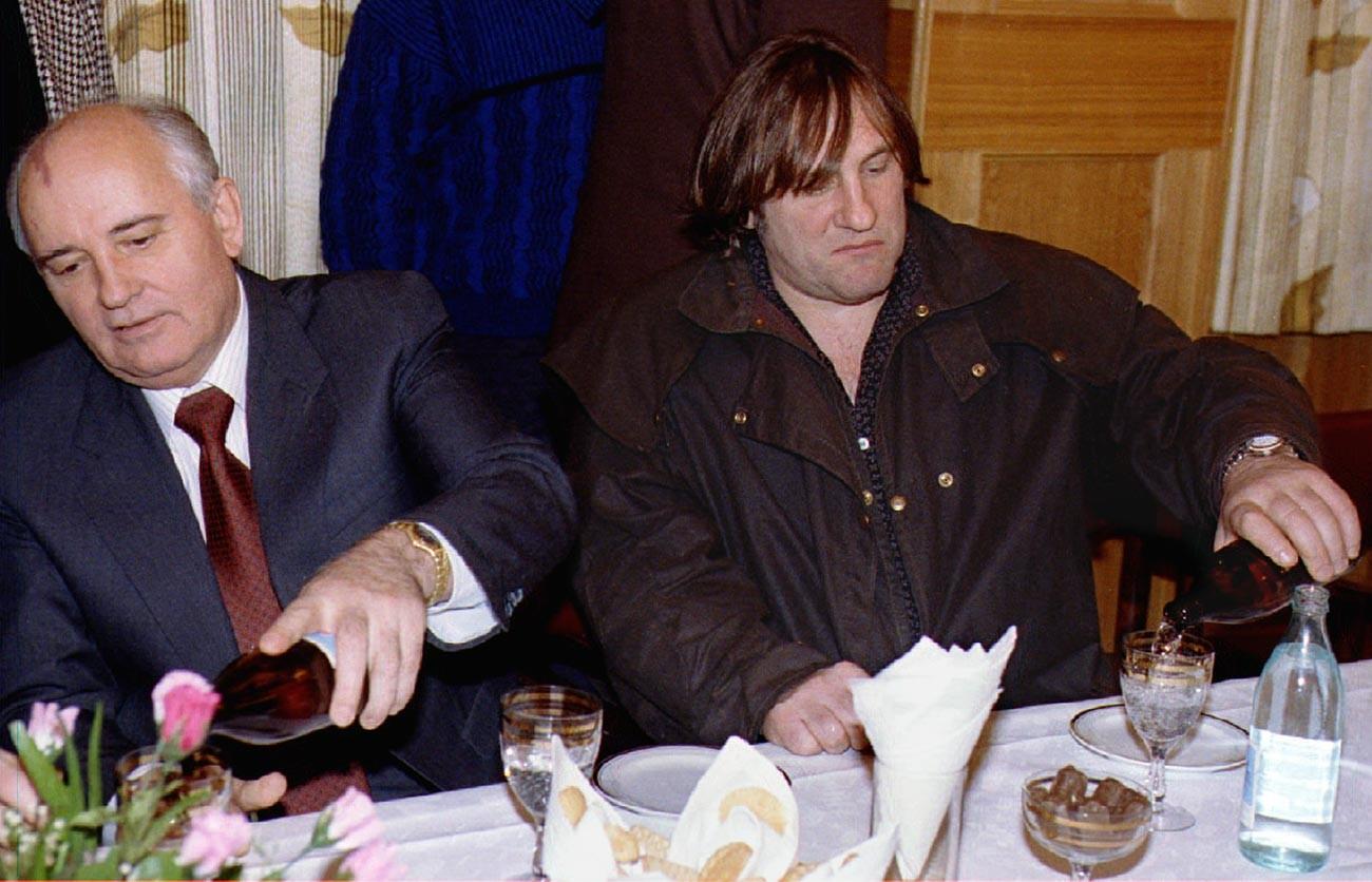 Бившият съветски лидер Михаил Горбачов (вляво) и френската филмова звезда Жерар Депардийо си наливат минерална вода  на среща в Москва. Тогава френският актьор идва на филмовия фестивал.