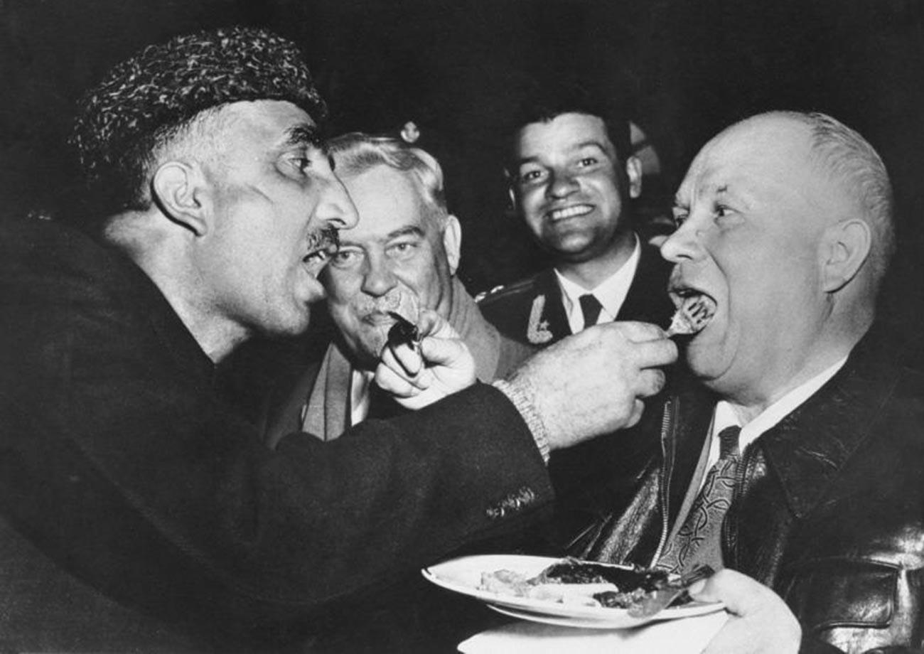 Primeiro-ministro do estado indiano de Jamu e Caxemira, Bakshi Ghulam Mohammad, e Nikita Khruschov durante sua visita à Índia em 1955. Alimentando-se mutuamente, um costume da hospitalidade da Caxemira