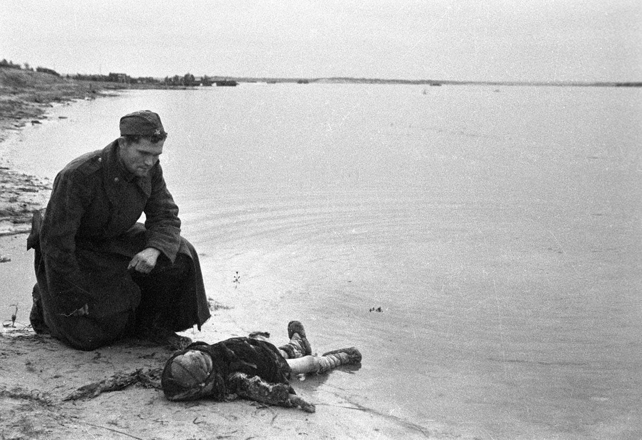 Un soldat soviétique au bord du Dniepr est en deuil d'un enfant assassiné par les nazis