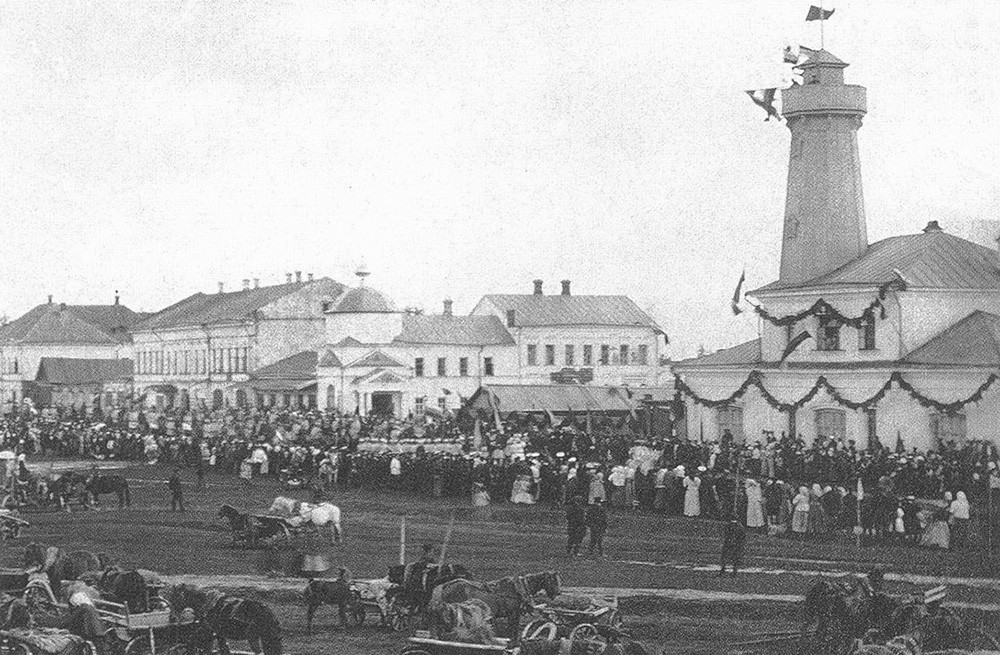 La Piazza del Commercio durante una festività. Sulla destra, la torre dei vigili del fuoco, costruita sul progetto dell'architetto A. M. Dostoevskij, fratello del celebre scrittore
