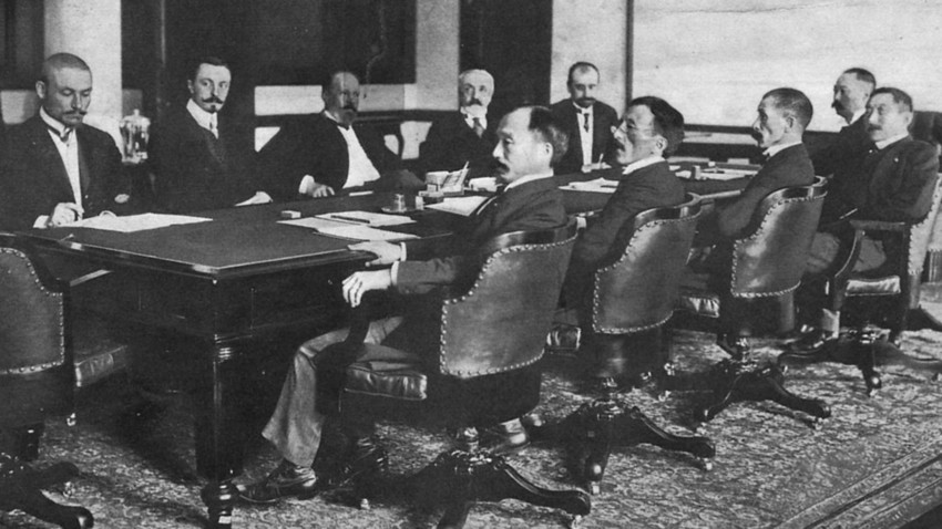 Delegaciji na portsmouthskih pogajanjih: ruska (na oddaljeni strani mize) Korostovec, Nabokov, Witte, Rosen in Plançon, ter japonska (na bližnji strani mize) Adači, Očiaj, Komura, Takahira in Sato