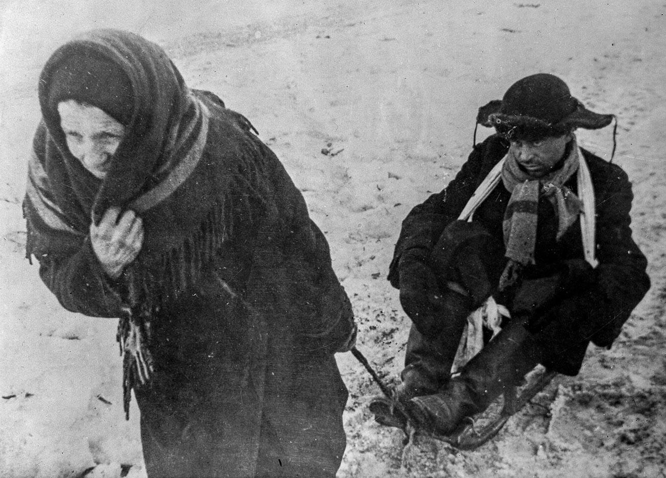 Блокада Лењинграда (8. септембар 1941. – 27 јануара 1944.). Жена вуче на санкама мужа исцрпљеног од глади. Велики отаџбински рат (1941-1945).
