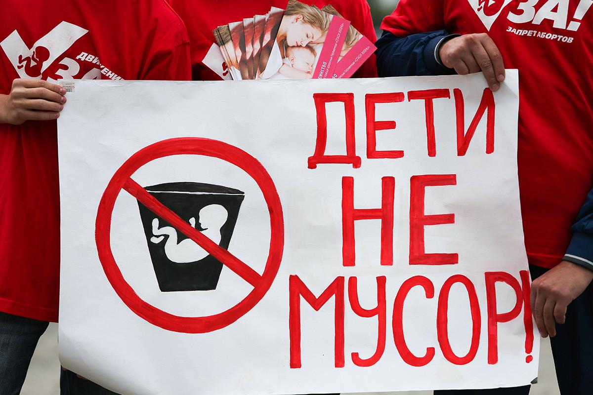"""Gli attivisti del movimento anti-aborto reggono un poster che dice """"Deti ne musor!"""" (""""I bambini non sono spazzatura"""") davanti a un centro prenatale"""