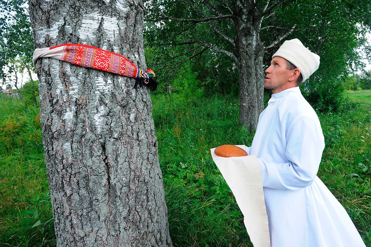 Molla (duhovnik) iz vasi Malaja Tavra, kjer živijo ljudje marijske narodnosti, izvaja molitveno slovesnost pri svetem drevesu.