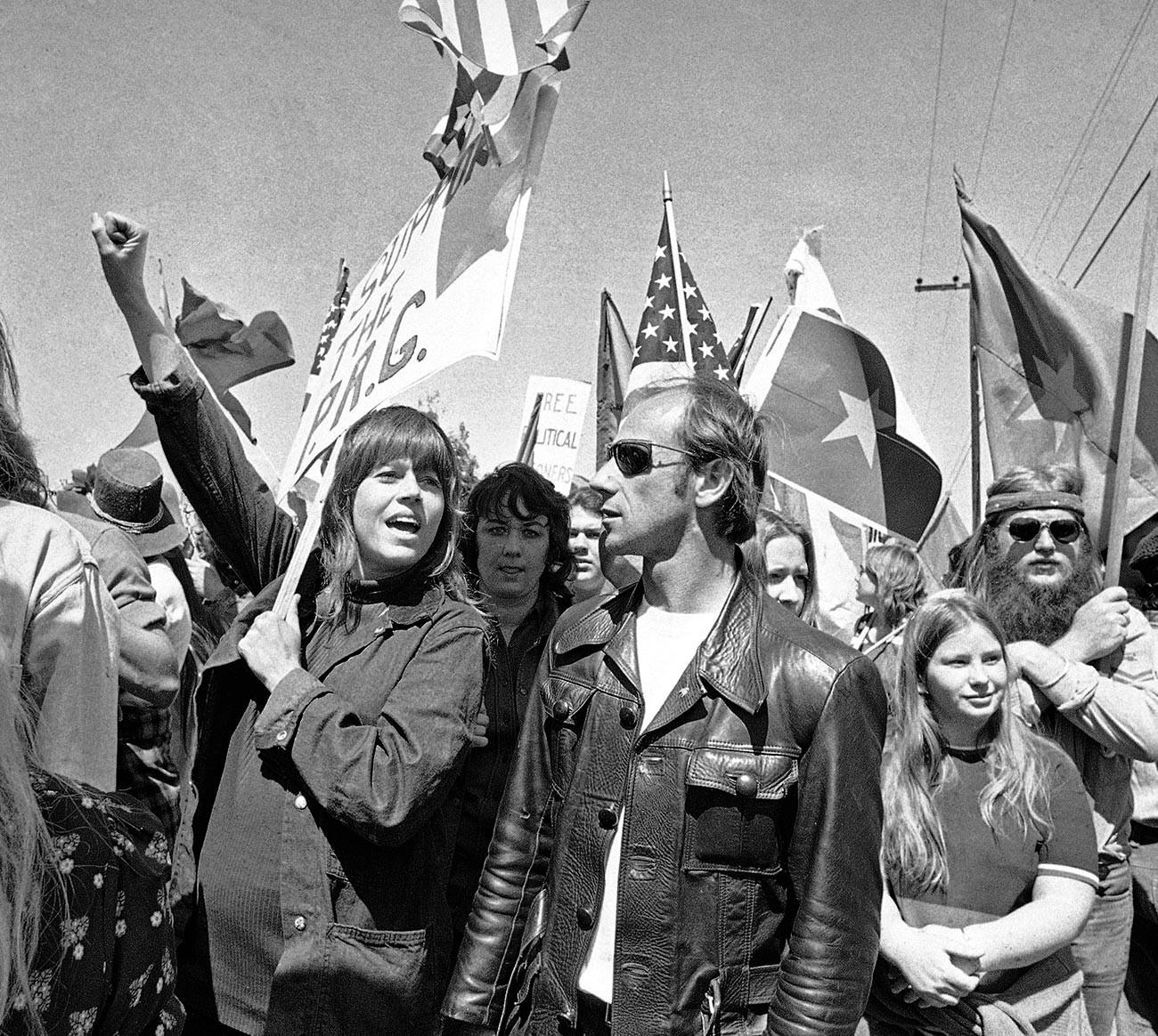 Актрисата Джейн Фонда вдига ръка във въздуха, докато се присъединява към група антивоенни демонстранти на марш към Западния Бял дом в знак на протест срещу посещението на президента на Южен Виетнам Нгуен Ван Тху в Сан Клементе, Калифорния, 2 април 1973 г.