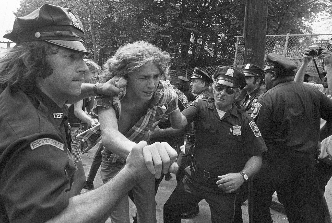 Младеж е задържан от полицията в Бостън пред гимназията на Южен Бостън , 13 септември 1974 г.